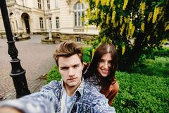Stylish happy hipster couple having fun traveling and taking selfies in the old city in europe in sunny spring time stock images