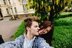 Stylish happy hipster couple having fun traveling and taking selfies in the old city in europe in sunny spring time royalty free stock images