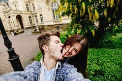 Stylish happy hipster couple having fun traveling and taking selfies in the old city in europe in sunny spring time stock image