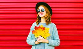 Stylish happy portrait smiling woman with yellow maple leaves Royalty Free Stock Photography