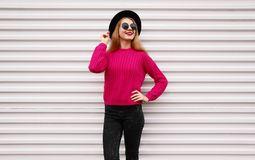 Stylish happy smiling woman in colorful pink knitted sweater, black round hat on white wall royalty free stock photography