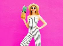 Stylish happy smiling woman holding pineapple wearing striped jumpsuit, summer round straw hat on colorful pink royalty free stock photography