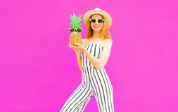 Stylish happy smiling woman holding pineapple wearing striped jumpsuit, summer round straw hat on colorful pink royalty free stock images