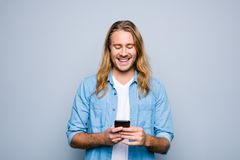 Stylish happy smiling young guy wearing casual clothes is having. A chat using his telephone, isolated on grey background Royalty Free Stock Photos