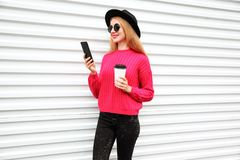 Stylish happy woman looking at phone holding coffee cup, female model wearing black round hat, pink knitted sweater in city. On white wall background stock photos