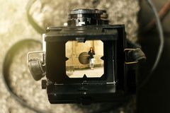 Stylish happy woman in viewfinder of  analog film camera on back. Ground of city old wall Stock Photo