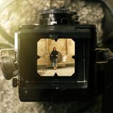 Stylish happy woman in viewfinder of  analog film camera on back. Ground of city old wall Royalty Free Stock Photo