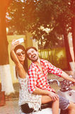 Stylish happy young couple making self picture on scooter Royalty Free Stock Image