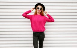 Stylish happy young woman in colorful pink knitted sweater, black round hat posing on city white wall. Background royalty free stock photography