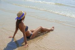 Stylish happy young woman relaxing on beach. girl sitting and tanning on beach near sea with waves, sunny warm weather. Summer. Vacation concept. Peaceful calm stock images