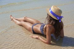 Stylish happy young woman relaxing on beach. girl sitting and tanning on beach near sea with waves, sunny warm weather. Summer. Vacation concept. Peaceful calm royalty free stock image