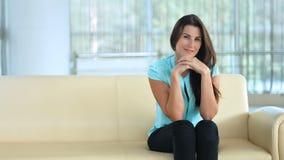 Stylish happy young woman sitting on a sofa. Beauty, fashion portrait stock video