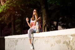 Stylish happy young woman in sunglasses, white sneakers. She holds coffee to go. portrait of smiling girl stock images