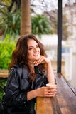 Stylish happy young woman in street cafe. She holds coffee to go. royalty free stock photos