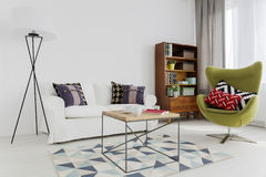 Stylish harmony of different furniture pieces. Room corner of a modern flat, with a designer swivel armchair and a modernist bookcase Stock Photos