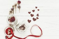 Stylish hearts in glass jar and roses on white rustic  wooden ba. Ckground in light . happy valentine`s day concept. greeting card flat lay with space for text Royalty Free Stock Images