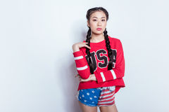 Stylish hipster asian girl in american patriotic outfit posing and looking at camera isolated on grey, Stock Image