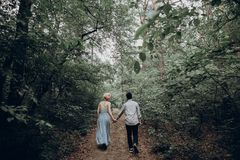 Stylish hipster bride and groom walking in green summer forest. Happy couple in love, modern outfit, relaxing at park. girl in dress and straw hat with peony royalty free stock image
