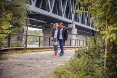 Stylish hipster couple. boho gypsy woman gently hugging arm of confident man under abandoned bridge. atmospheric sensual moment. r Stock Photo