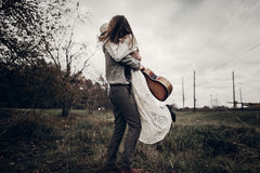 Stylish hipster couple dancing in windy field. boho gypsy woman stock photos