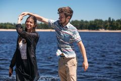 Stylish hipster couple dancing at windy river in summer city. ha royalty free stock images