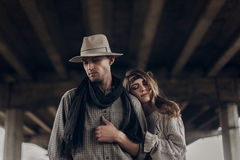 Stylish hipster couple dreaming under abandoned bridge. boho gyp. Sy women gently hugging arm of confident men in hat. atmospheric sensual moment. rustic Stock Images