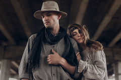 Stylish hipster couple dreaming under abandoned bridge. boho gyp. Sy women gently hugging arm of confident men in hat. atmospheric sensual moment. rustic Stock Image