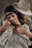Stylish hipster couple gently hugging. man in hat sensual touching boho woman in knitted sweater. atmospheric sensual moment. Stylish hipster couple gently stock photos