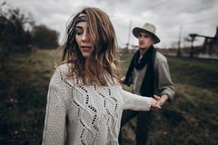 Stylish hipster couple holding sensually hands. boho gypsy woman. Stylish hipster couple holding sensually hands. boho gypsy women and men in hat embracing in royalty free stock photography