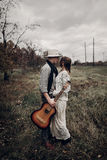 Stylish hipster couple hug in field, handsome cowboy musician wi Royalty Free Stock Photo
