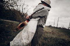 Stylish hipster couple hug in field, handsome cowboy musician wi Stock Photo