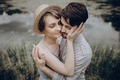 Stylish hipster couple hugging at lake. man and woman in modern. Stylish hipster couple hugging at lake. men and women in modern outfit, in love relaxing in royalty free stock image