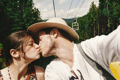 Stylish hipster couple kissing on chairlift  in summer mountains. Travel together concept Royalty Free Stock Photos