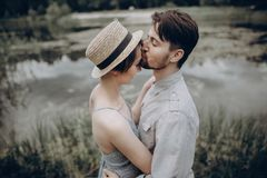 Stylish hipster couple kissing at lake. man and woman embracing, in love relaxing in summer park, picnic date. girl in. Stylish hipster couple kissing at lake stock images