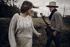 Stylish hipster couple posing. man in hat with guitar and his bo Stock Photography