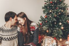 Stylish hipster couple in sweaters hugging and embracing at chri. Stmas tree in cozy evening room. atmospheric moments. merry christmas and happy new year Royalty Free Stock Photos