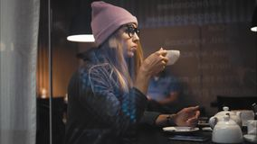 A stylish hipster female in glasses using smart watch and using app on a smartphone in a cafe. View through the window Royalty Free Stock Photos