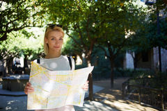 Stylish hipster girl with atlas in hands seeking the way to her hotel during summer adventure Stock Photography