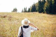 Stylish hipster girl with backpack traveling in sunny mountains. Woman in hat exploring and hiking on top of mountain in sunny stock images