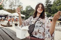 Stylish hipster girl eating wok noodles with vegetables from carton box with bamboo chopsticks. Asian Street food festival. Happy stock photos