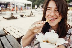 Stylish hipster girl eating wok noodles with vegetables from carton box with bamboo chopsticks. Asian Street food festival. Happy stock image