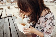 Stylish hipster girl eating wok noodles with vegetables and seafood from carton box with bamboo chopsticks. Asian Street food stock photos