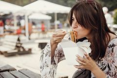 Stylish hipster girl eating wok noodles with vegetables and seafood from carton box with bamboo chopsticks. Asian Street food stock images