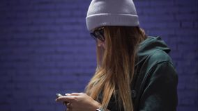 A stylish hipster girl in fashionable glasses and a hat using app on smartphone near a brick violet wall.  stock footage