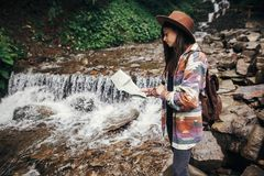 Stylish hipster girl in hat with backpack exploring map, standin. G at river with waterfall in mountains. traveler woman traveling in woods. travel and Stock Image