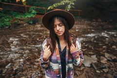 Stylish hipster girl in hat with backpack relaxing in forest in. Mountains. traveler woman exploring summer woods. travel and wanderlust concept. atmospheric Stock Images