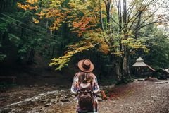 Stylish hipster girl in hat with backpack walking in forest in m. Ountains. traveler woman exploring woods. travel and wanderlust concept. atmospheric moment Stock Photo