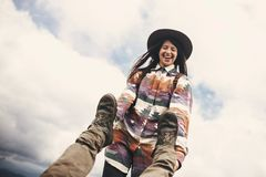 Stylish hipster girl in hat holding legs of falling man, funny moment on top of mountains. Happy young woman having fun and. Smiling with man. Travel and stock images