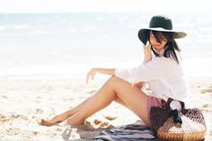 Stylish hipster girl in hat sitting on beach and tanning near sea waves. Summer vacation. Happy boho woman relaxing and enjoying. Sunny warm day at ocean. Space royalty free stock photography