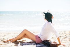 Stylish hipster girl in hat sitting on beach and tanning near sea waves. Summer vacation. Happy boho woman relaxing and enjoying. Sunny warm day at ocean. Space stock photo